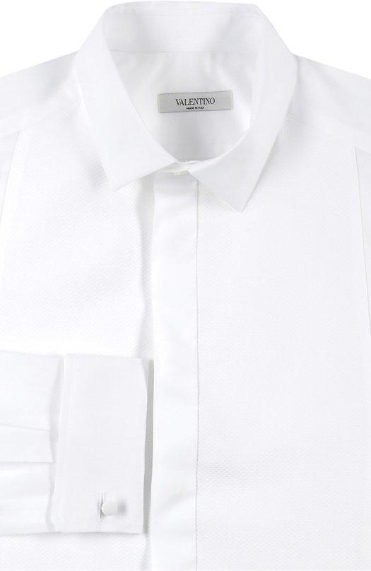 Сорочка с закрытой планкой и манжетами под запонки ValentinoРубашки<br>Для производства сорочки с длинным рукавом французского типа использован мягкий хлопок белого цвета. Модель из весенне-летней коллекции марки, основанной Валентино Гаравани, застегивается на потайные пуговицы. Рекомендуем сочетать с черным смокингом, галстуком-бабочкой и асимметричными запонками.<br><br>Российский размер RU: 50<br>Пол: Мужской<br>Возраст: Взрослый<br>Размер производителя vendor: 41<br>Материал: Хлопок: 100%;<br>Цвет: Белый